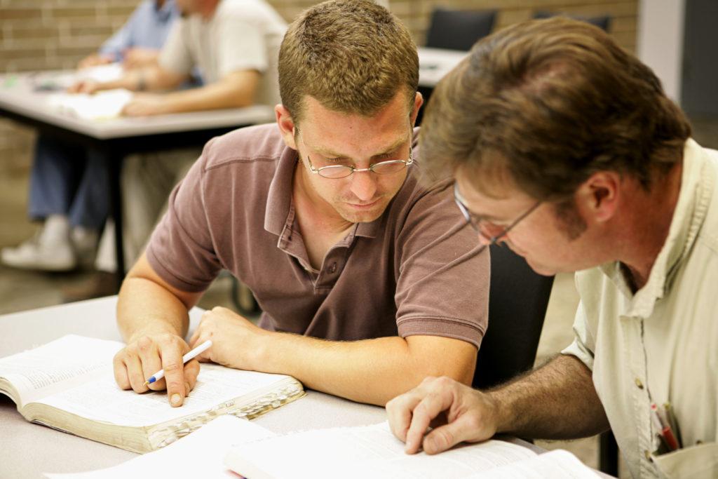 Dos alumnos adultos estudian juntos en clase.
