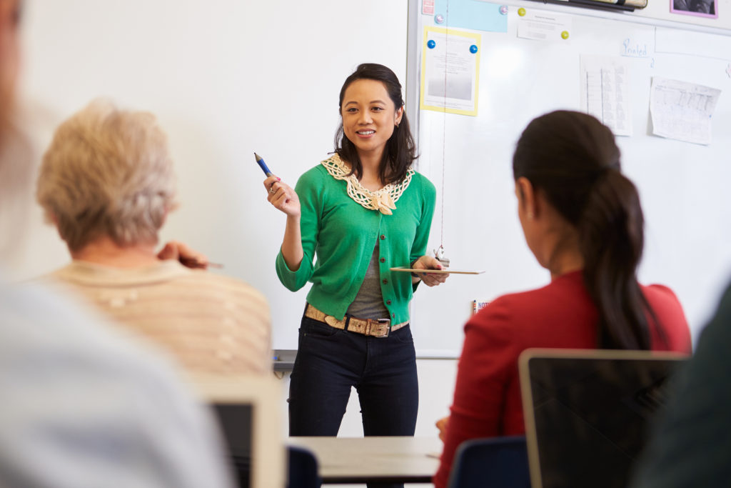 Teacher in front of students at an adult education class